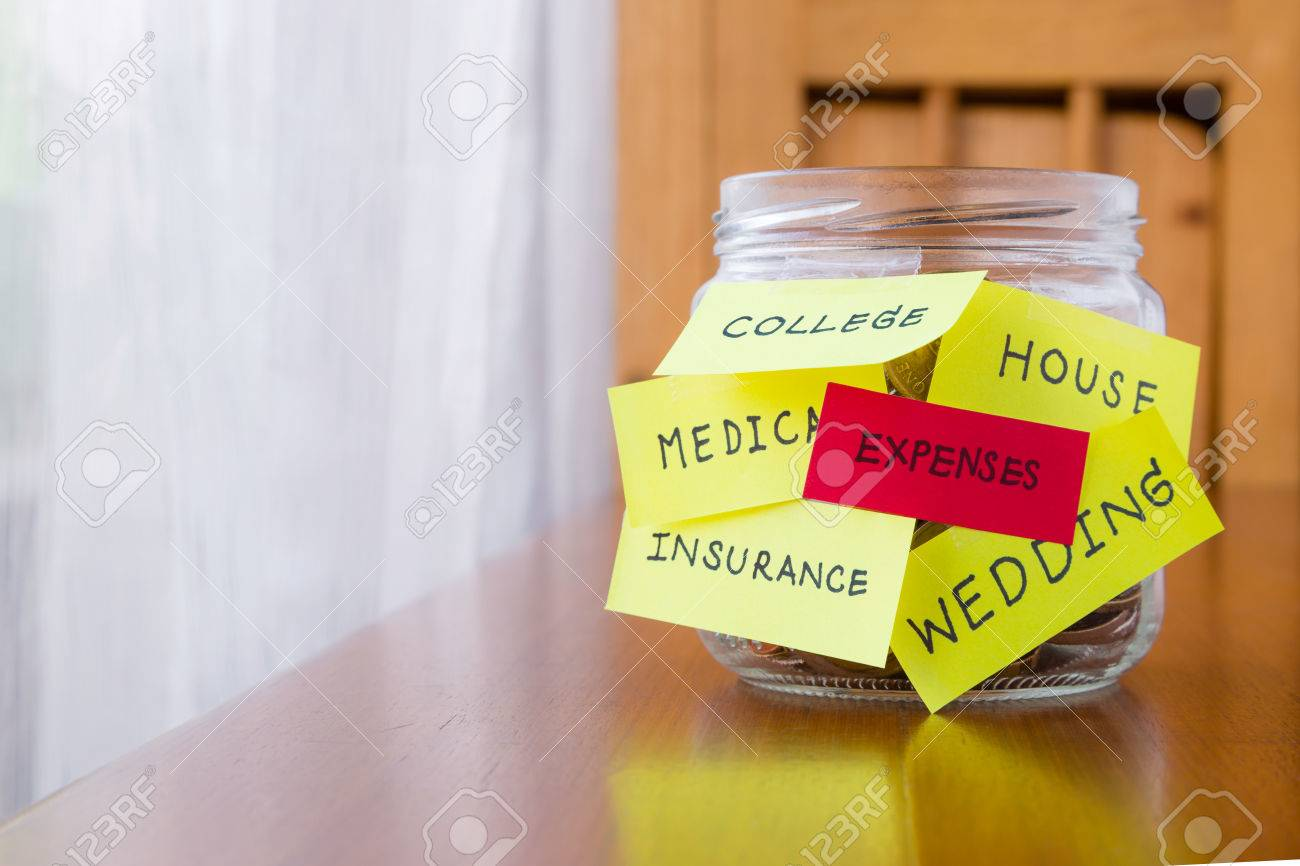 A jar of coins with expenses and other words or labels on savings money jar - 32767332