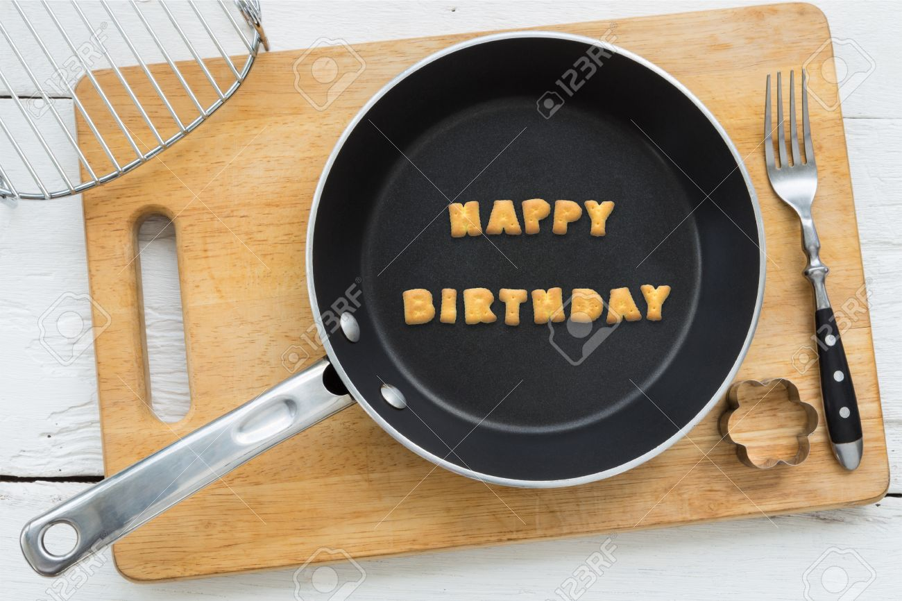 stock photo top view of letter collage made of biscuits word happy birthday putting in black frying pan other cooking equipments fork cookie cutter and