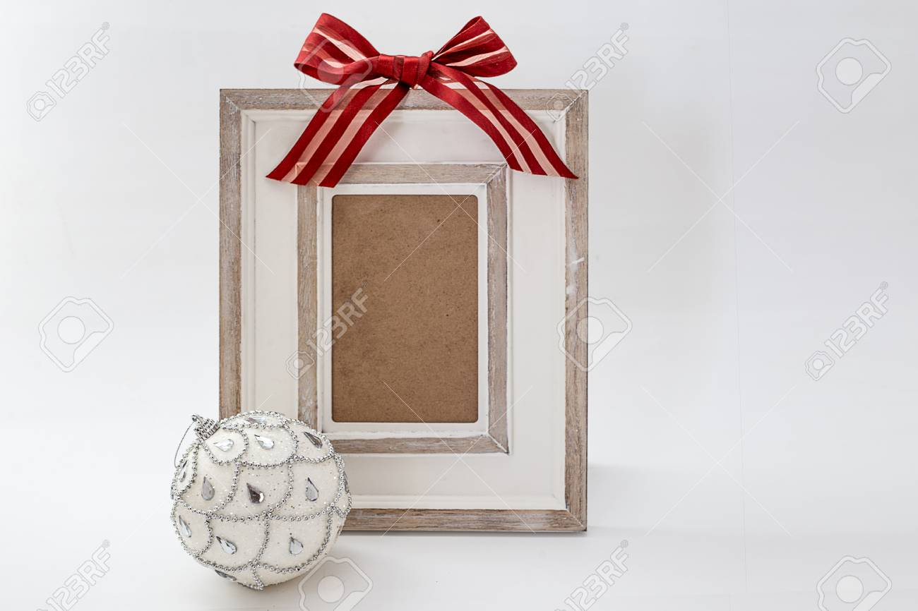 Picture Frame Decorated With Red Ribbon And Christmas Ball Isolated