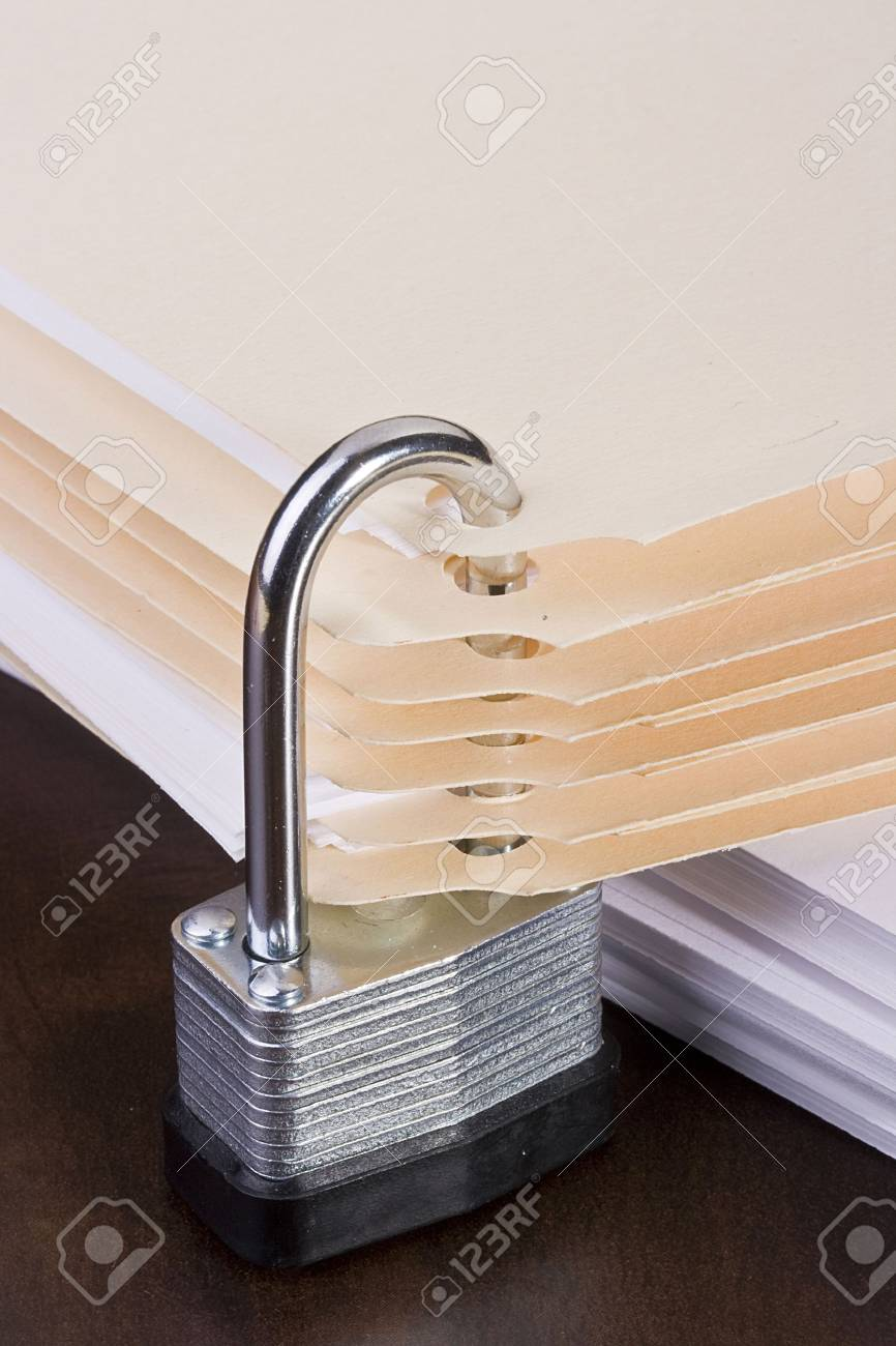 Stack of manila folders closed with a metal lock. Stock Photo - 8075401
