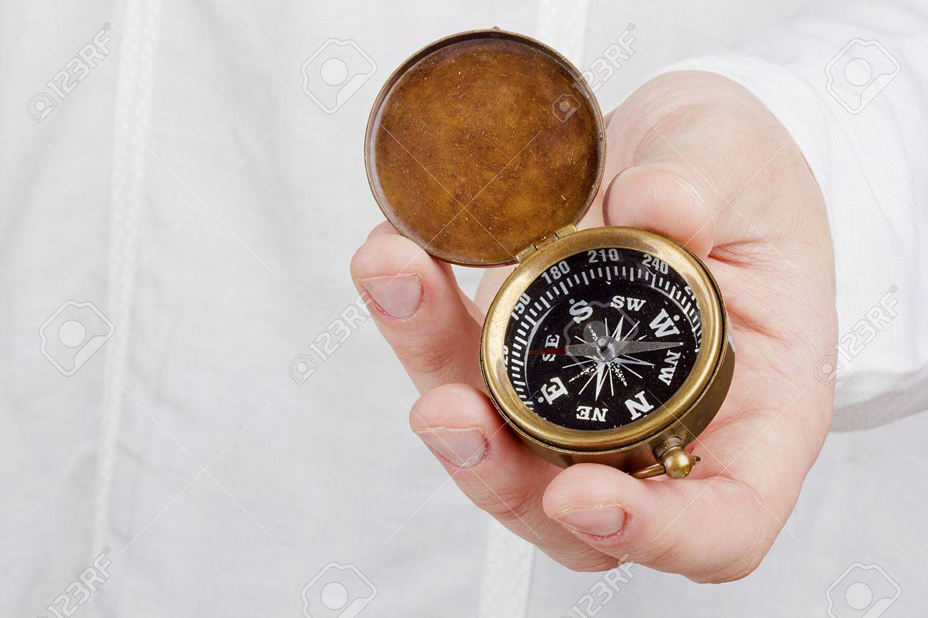 Close-up photograph of a hand holding an old compass. Stock Photo - 14456276