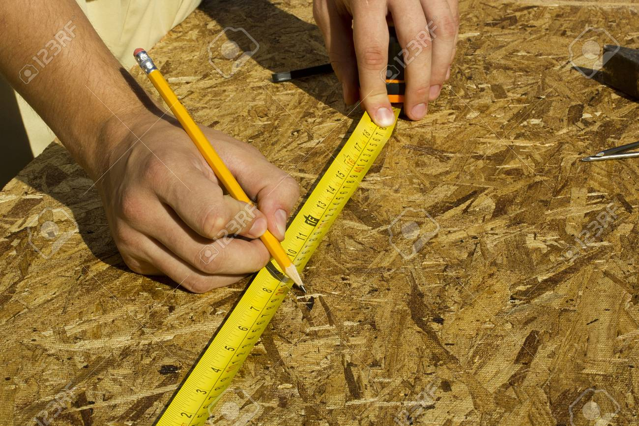 Closeup view of a worker measuring a section of plywood. Stock Photo - 14748537