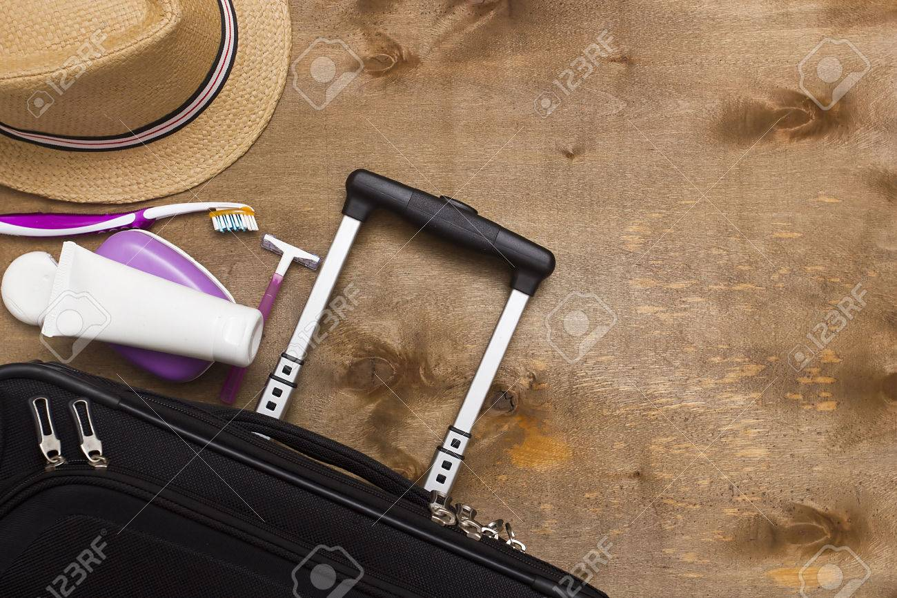 Suitcase traveler, toiletries and a hat on a wooden background. - 53631269