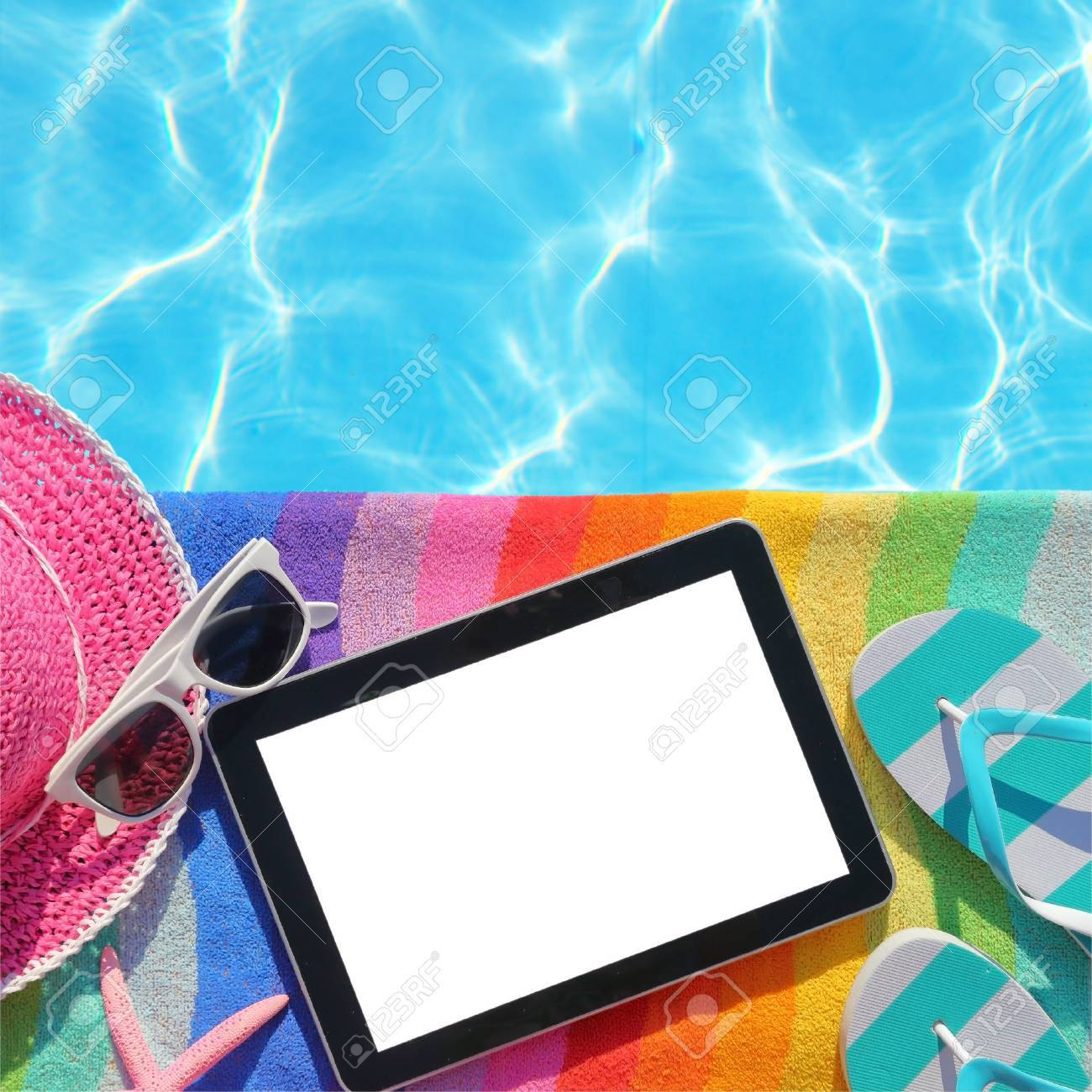Tablet with blank screen by poolside with beach accessories Stock Photo - 30688933