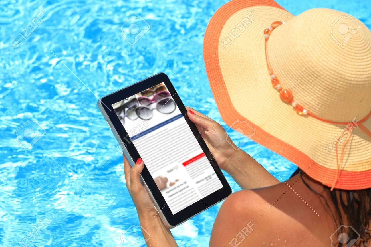 Woman holding tablet computer in the pool Stock Photo - 30690404