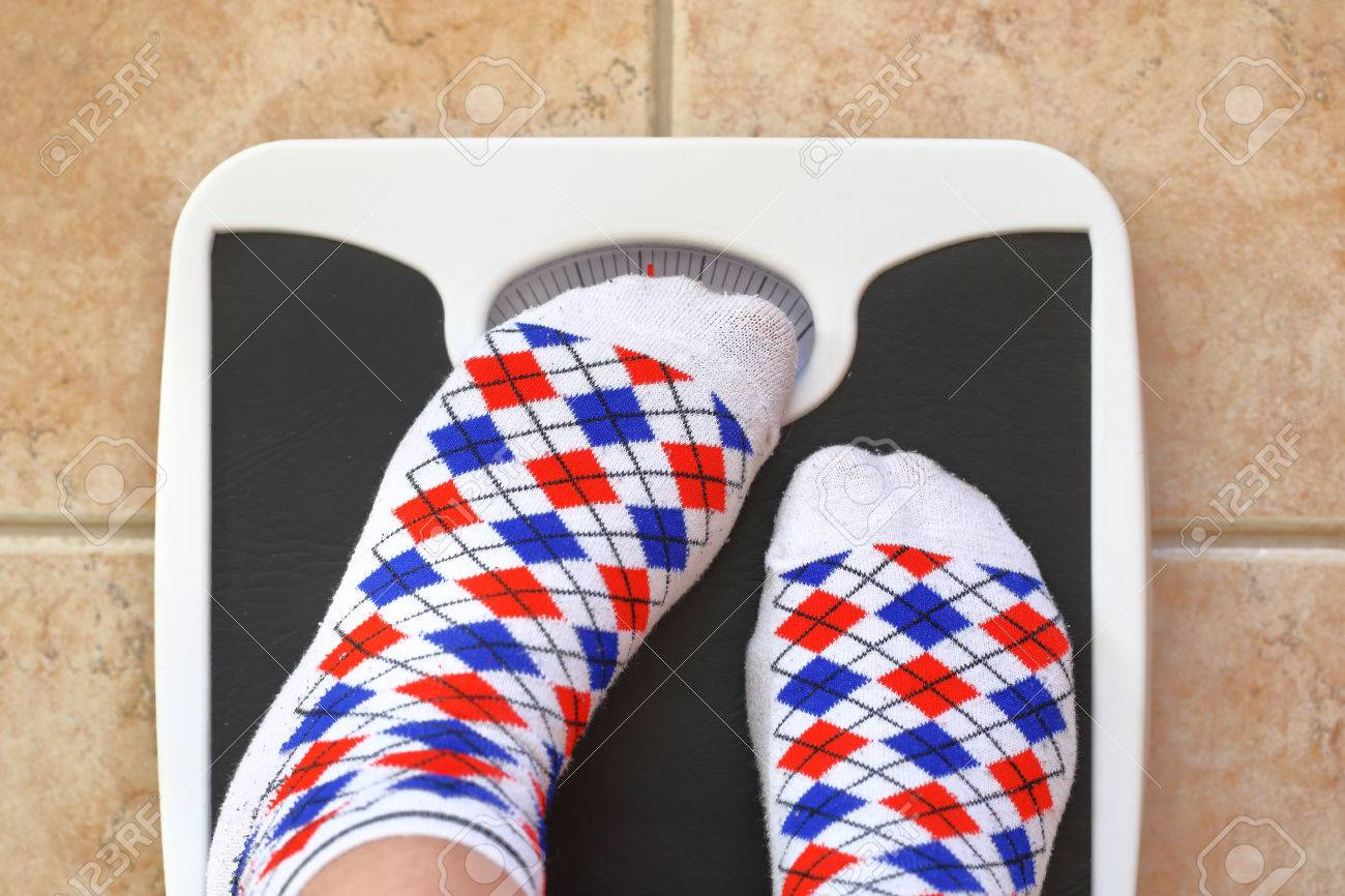 Woman's feet on bathroom scale. Diet concept Stock Photo - 37490636