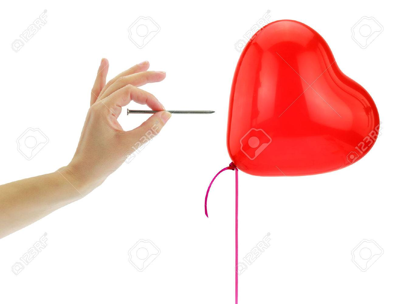 Nail about to pop a heart balloon isolated on white Stock Photo - 38694410