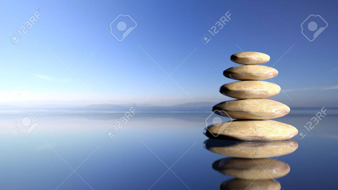 Zen stones stack from large to small in water with blue sky and peaceful landscape background. - 50022783