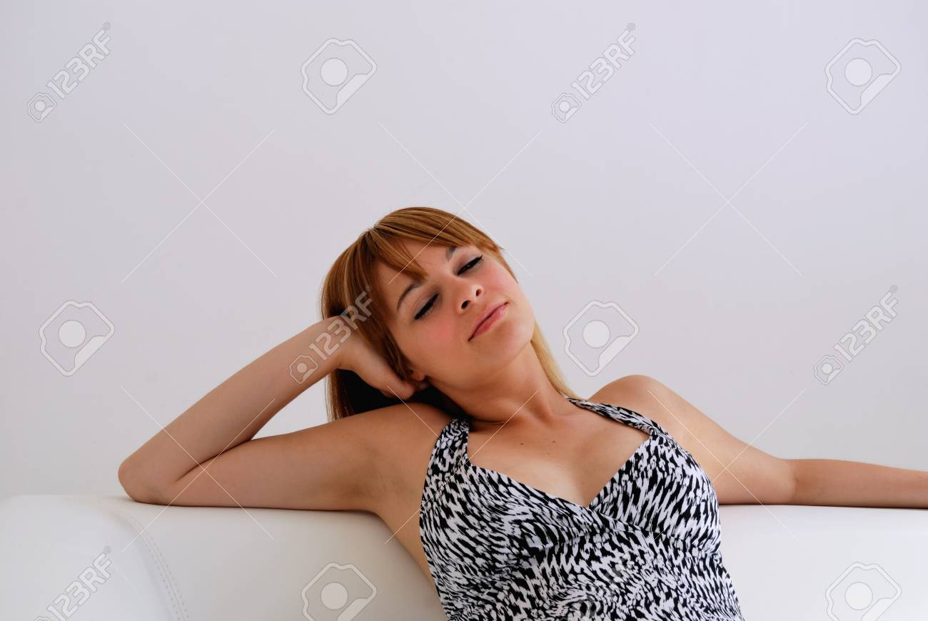 Portrait of young attractive woman comfortably sitting in white sofa, with closed eyes, expresses enjoying  She s wearing black and white dress against white background Stock Photo - 12708265
