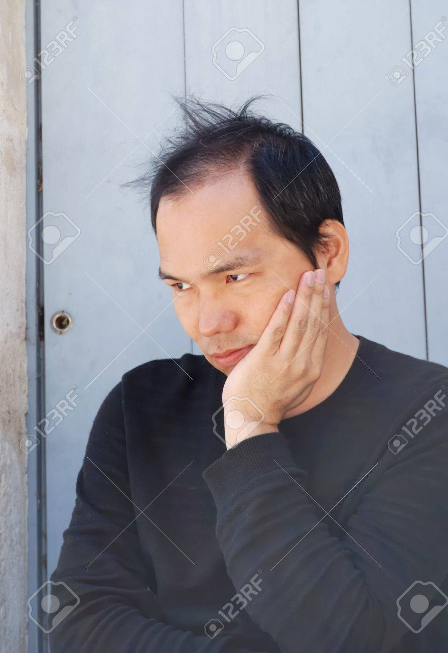 outdoor portrait of a young asiatic man thinking  and looking ahead against an antic blue door for background Stock Photo - 12984247