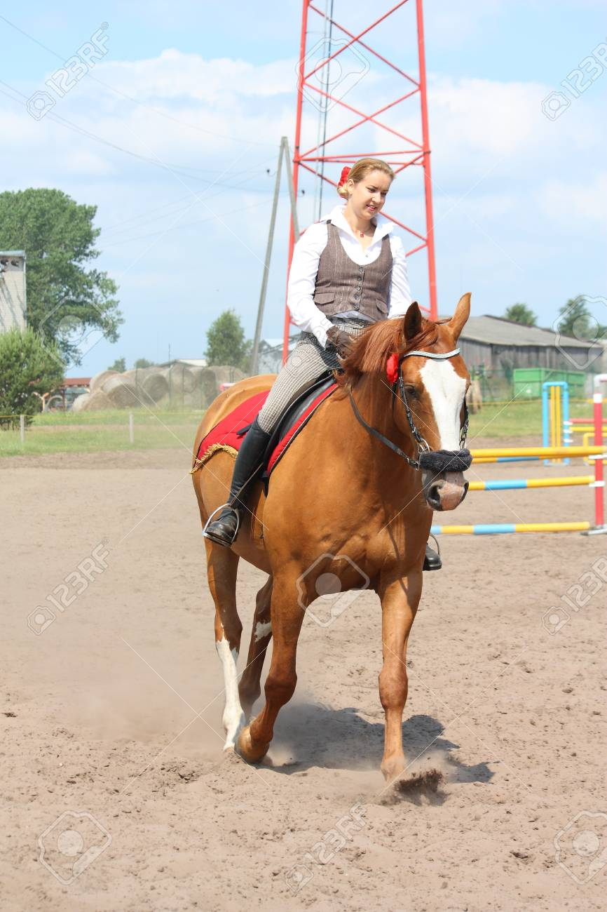 Beautiful young blonde woman riding trotting chestnut horse Stock Photo - 16336504