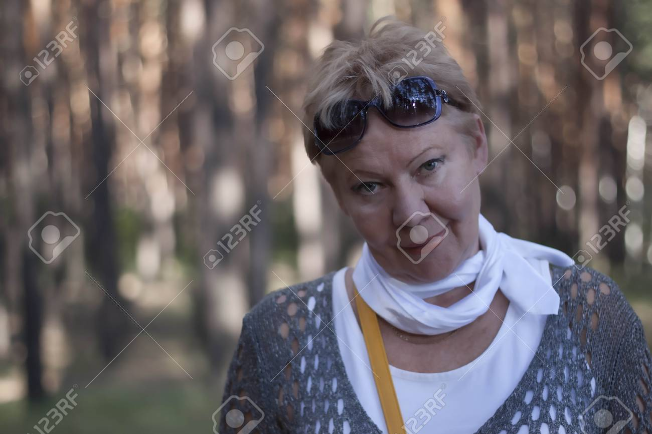 Portrait of a mature woman with sunglasses on his forehead with a blurred  forest background Stock