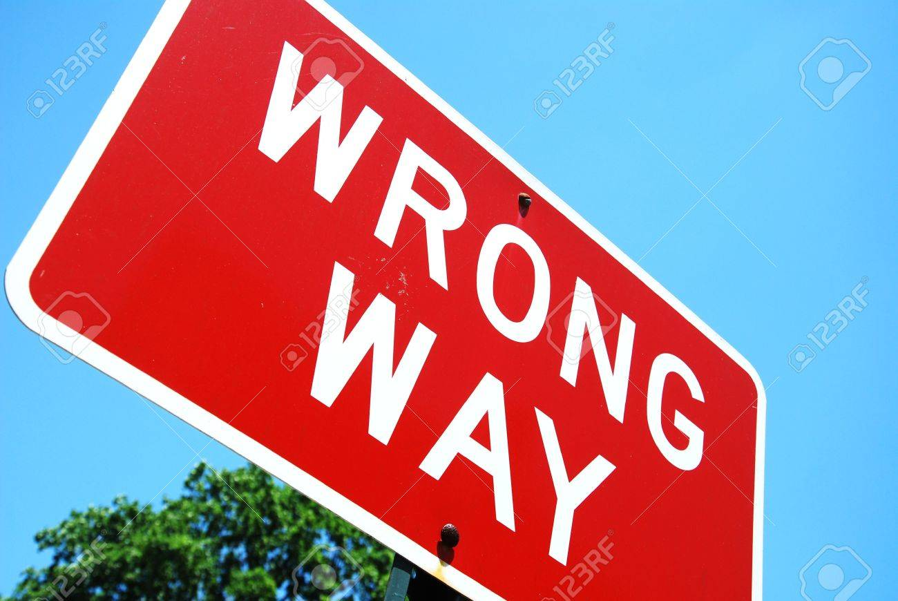 wrong way road sign on a blue sky background Stock Photo - 15690436