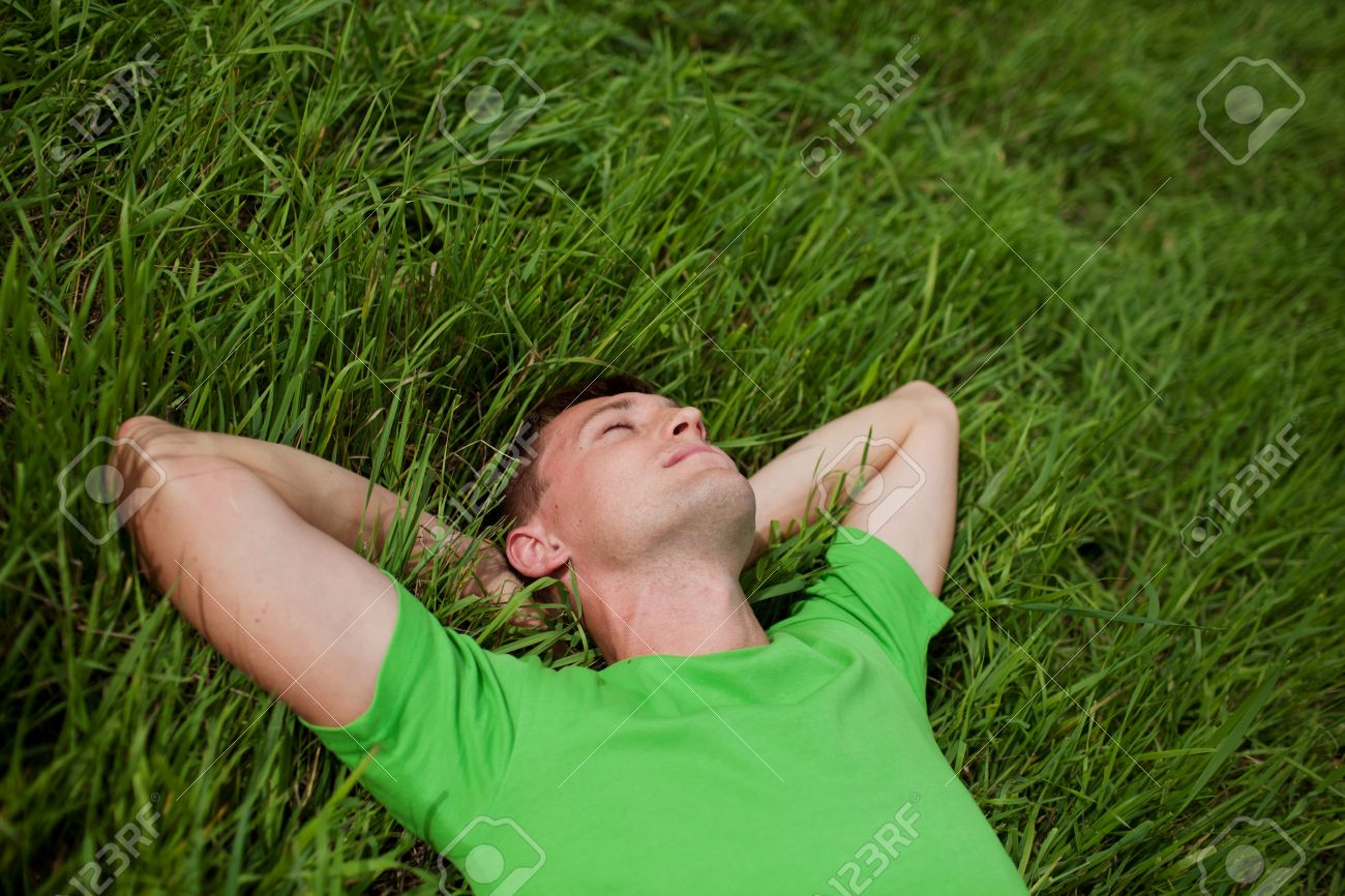 young man lying on the grass with his hands behind his head Stock Photo - 10233060