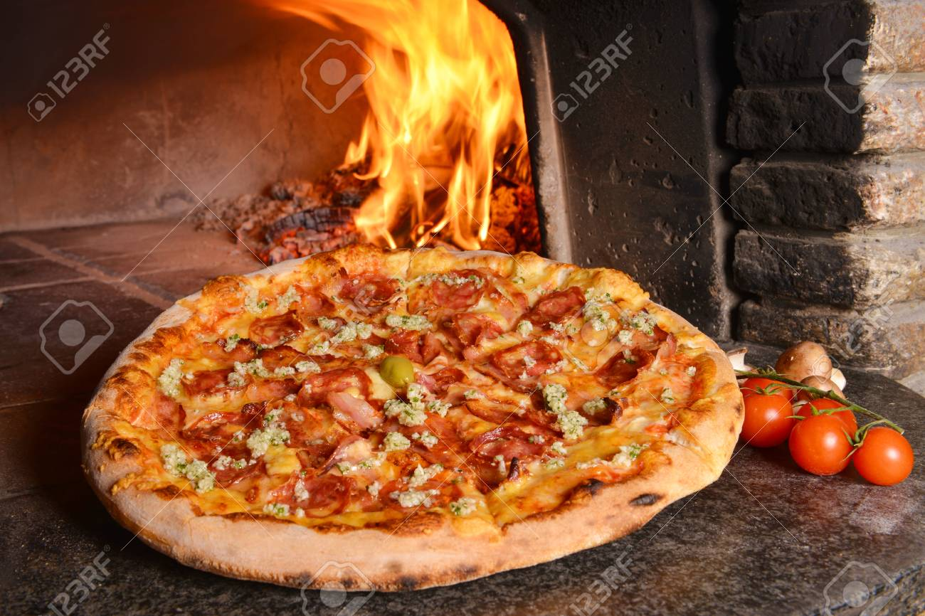 Baked tasty pizza with salami, garlic and bacon near oven - 32767689