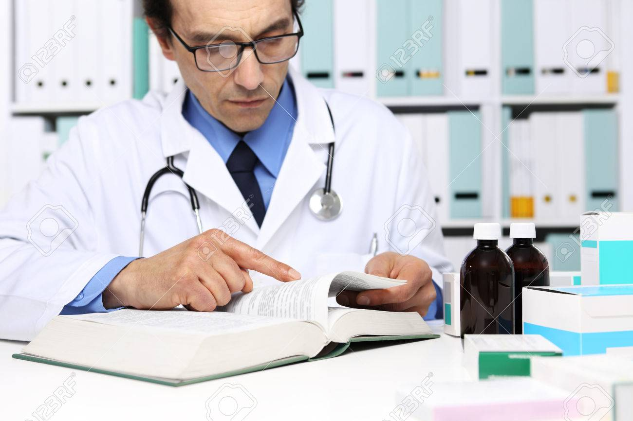 doctor reading a medical book in office desktop. health care