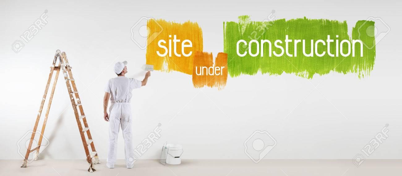 Homme Peintre Avec Dessin De Brossage De Peinture En Texte De Construction Isolé Sur Le Mur Blanc Vierge