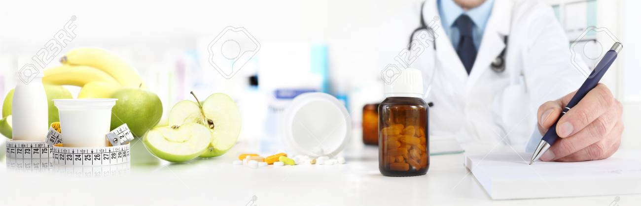 Nutritionist doctor writes the medical prescription for a correct diet on a desk with fruits, drugs and supplements, web banner and copy space template. - 91312483