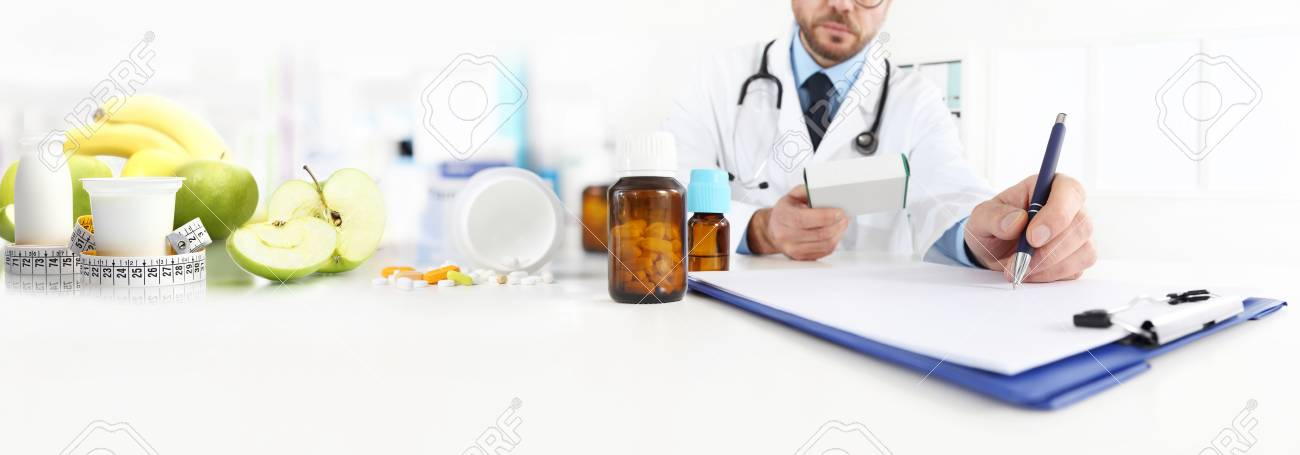 Nutritionist doctor writes the medical prescription for a correct diet on a desk with fruits, drugs and supplements, web banner and copy space template. - 91698652