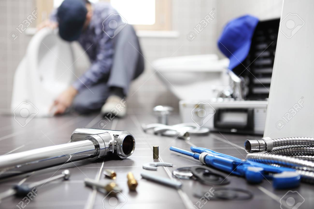 plumber at work in a bathroom, plumbing repair service, assemble and install concept. - 95572070