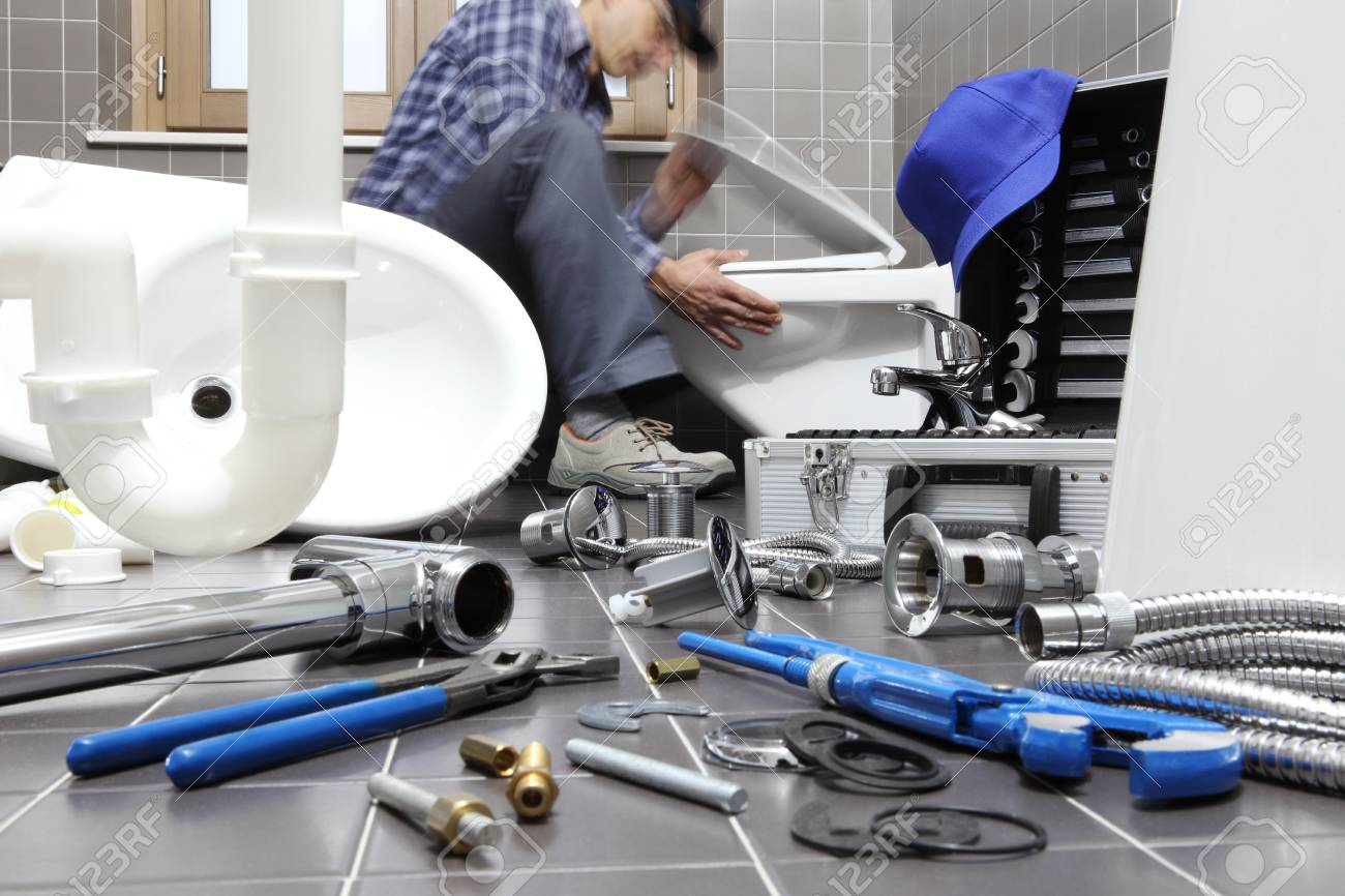 Plumber At Work In A Bathroom Plumbing Repair Service Assemble - Bathroom repair services