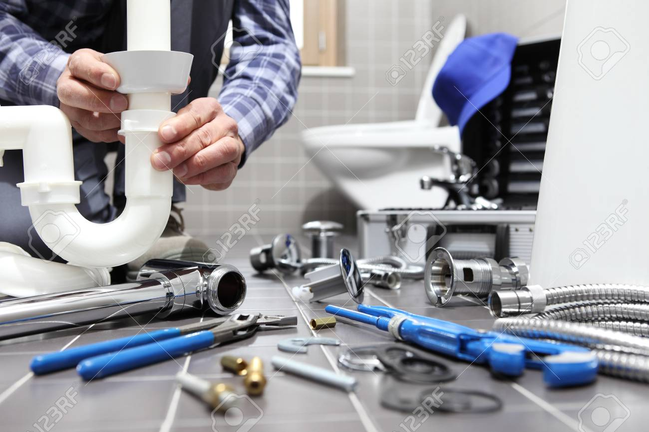 plumber at work in a bathroom, plumbing repair service, assemble and install concept. - 99466254