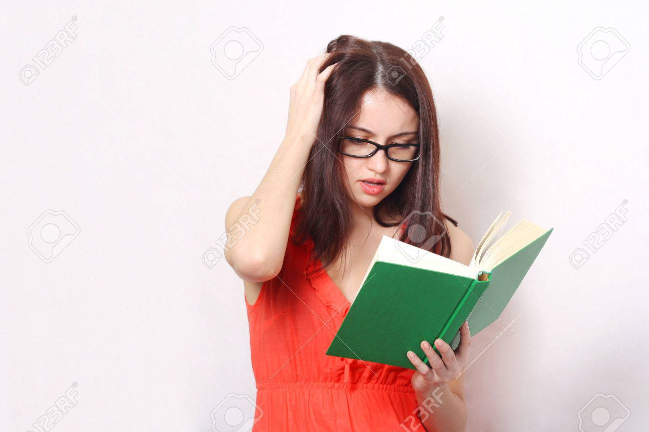 young brunette concentrated woman with glasses reading a book