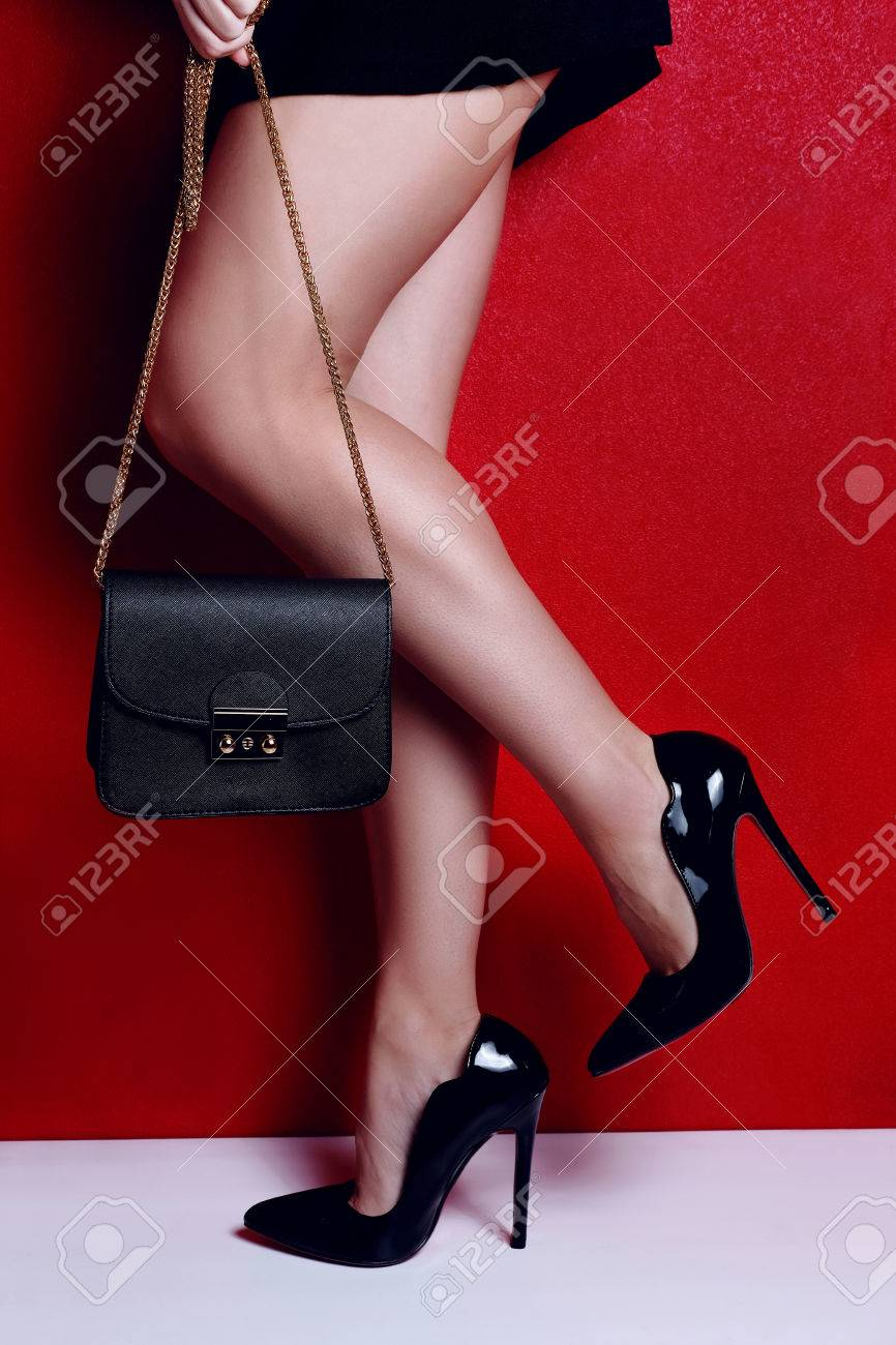 7cf2b38b2c98 Stock Photo - woman shapely legs wearing black lacquered high heel shoes  with little black handbag. Close up view