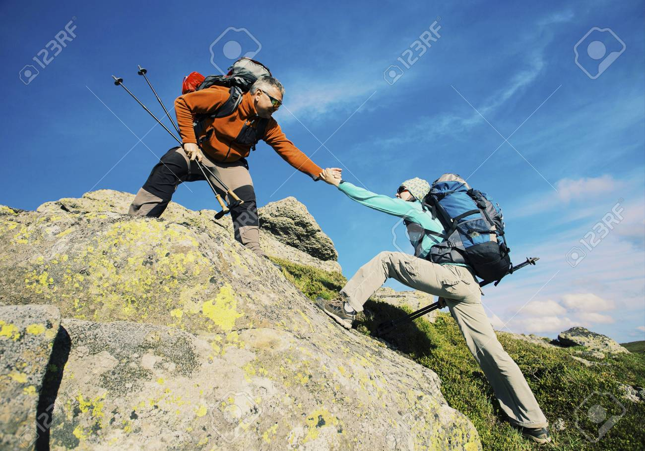 Couple Man and Woman help giving hands climbing rocky mountains Love and Travel Lifestyle concept hiking adventure vacations outdoor - 93206255