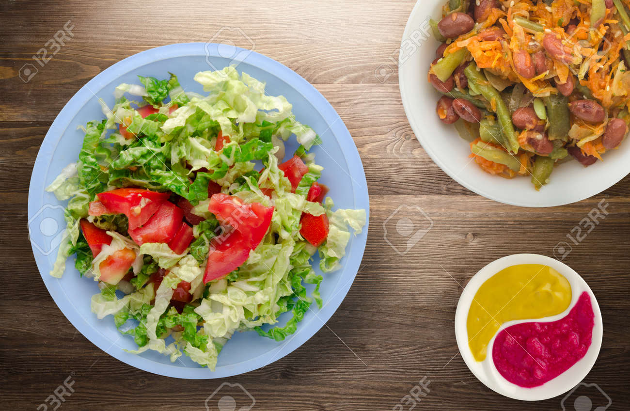 vegetarian food . salad of cabbage tomato on a light blue plate on a wooden background. healthy food - 135817761