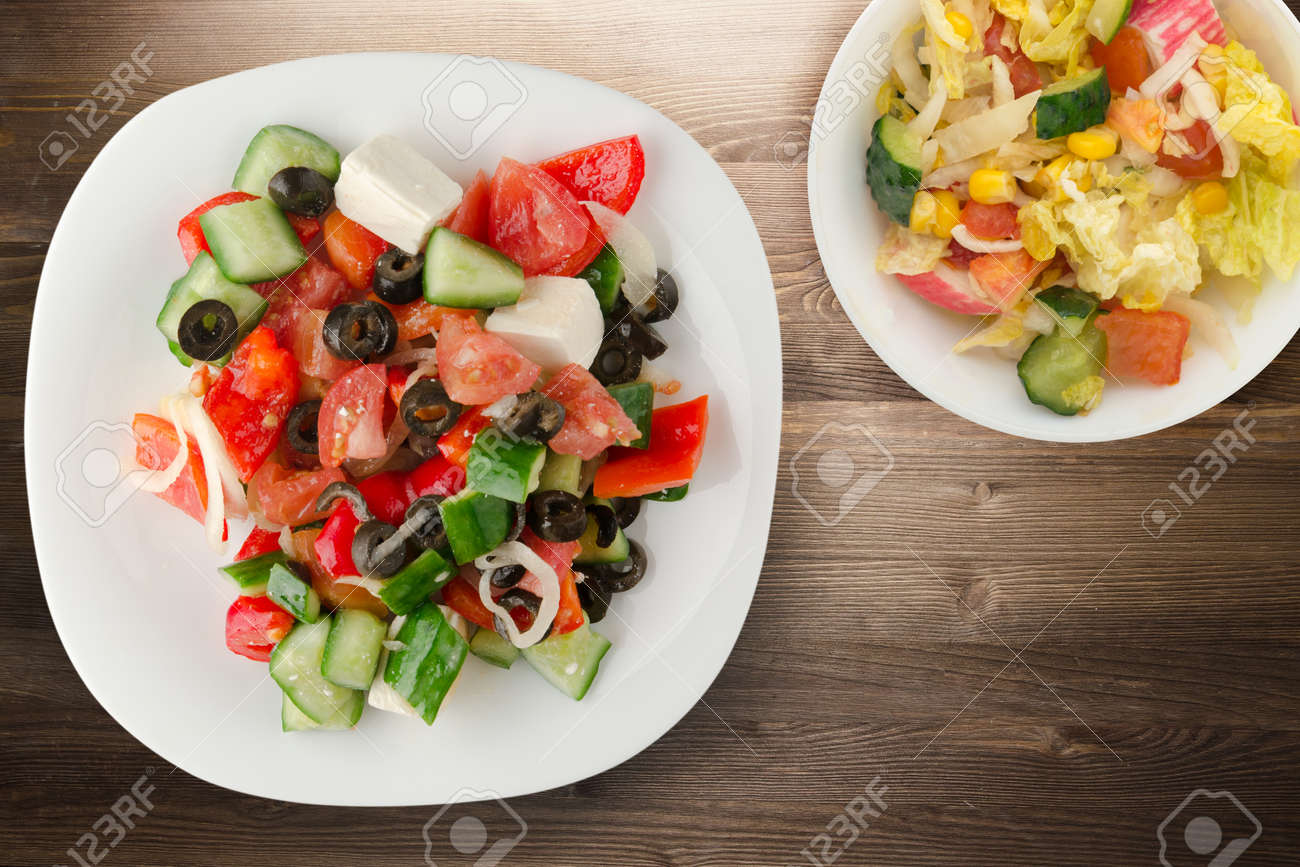 Greek salad on brown wooden background. Greek salad on white plate with vegetarian salad top view. healthy food - 156411220