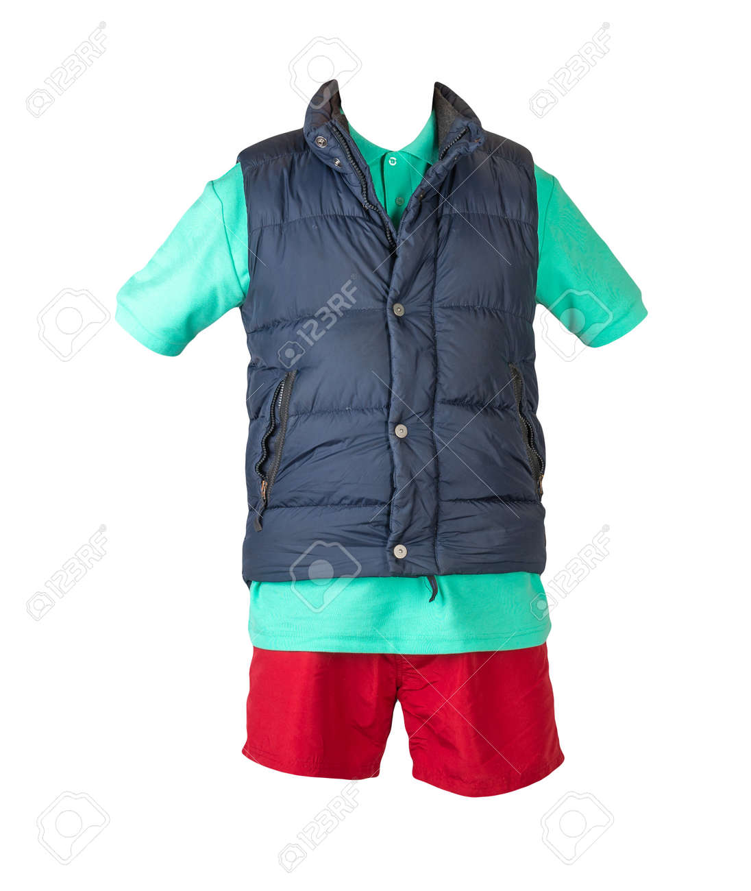 Dark blue sleeveless jacket, green t-shirt with collar on buttons and red sports shorts, isolated on white background. Current clothes for cool weather - 172140038