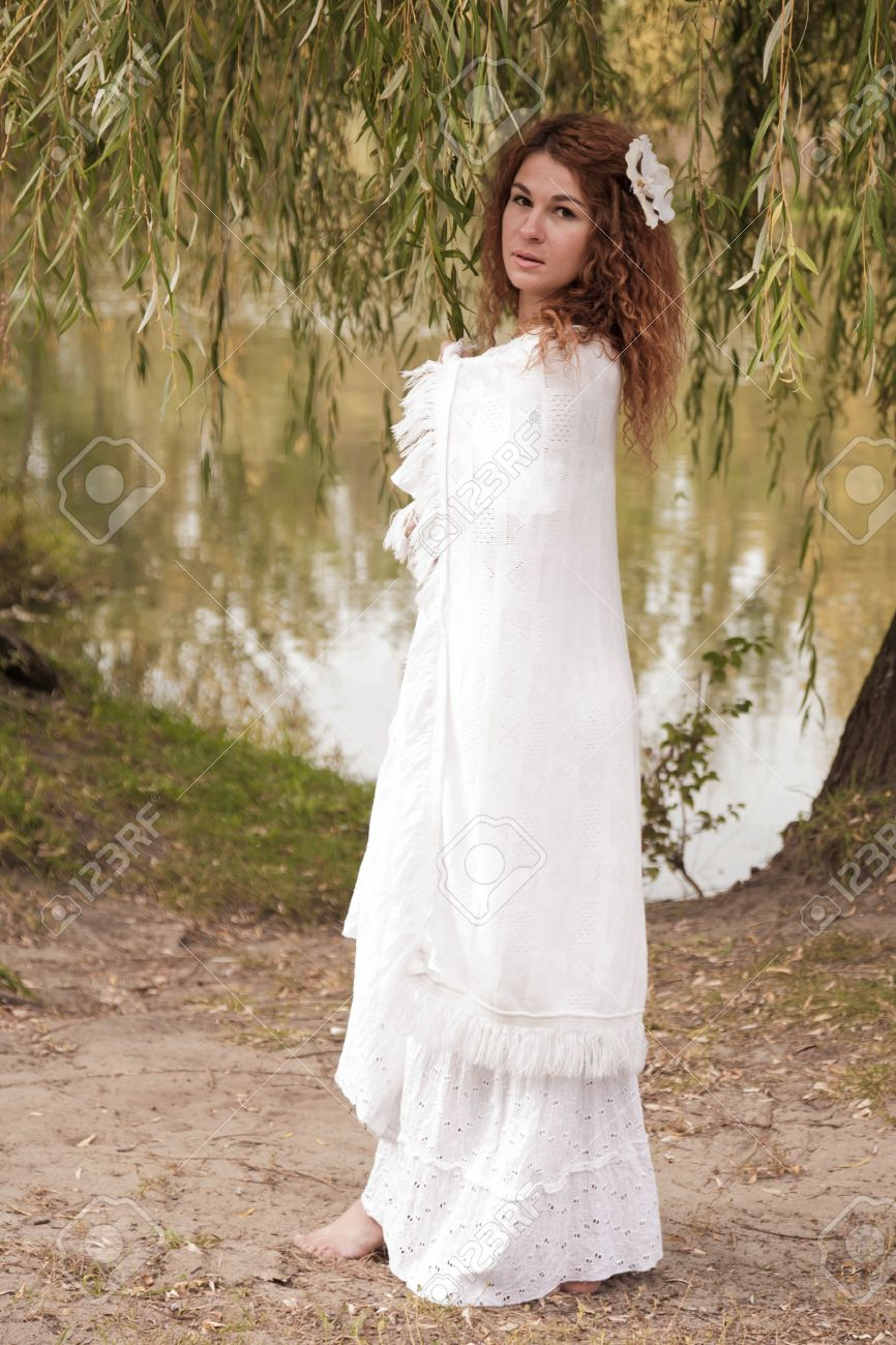 Barefoot young woman in white dress and white robe, walking along the river. Retro style. Stock Photo - 15739866