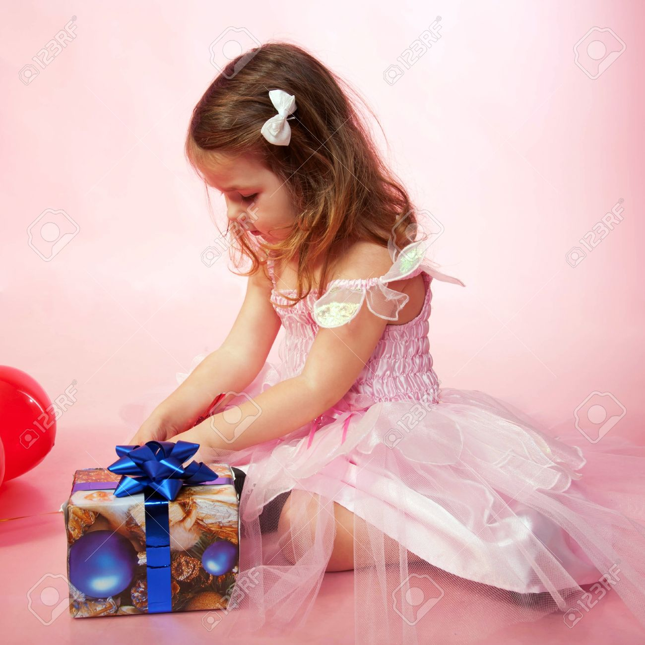Little Child Wearing Pink Dress Rejoicing And Looking On Christmas