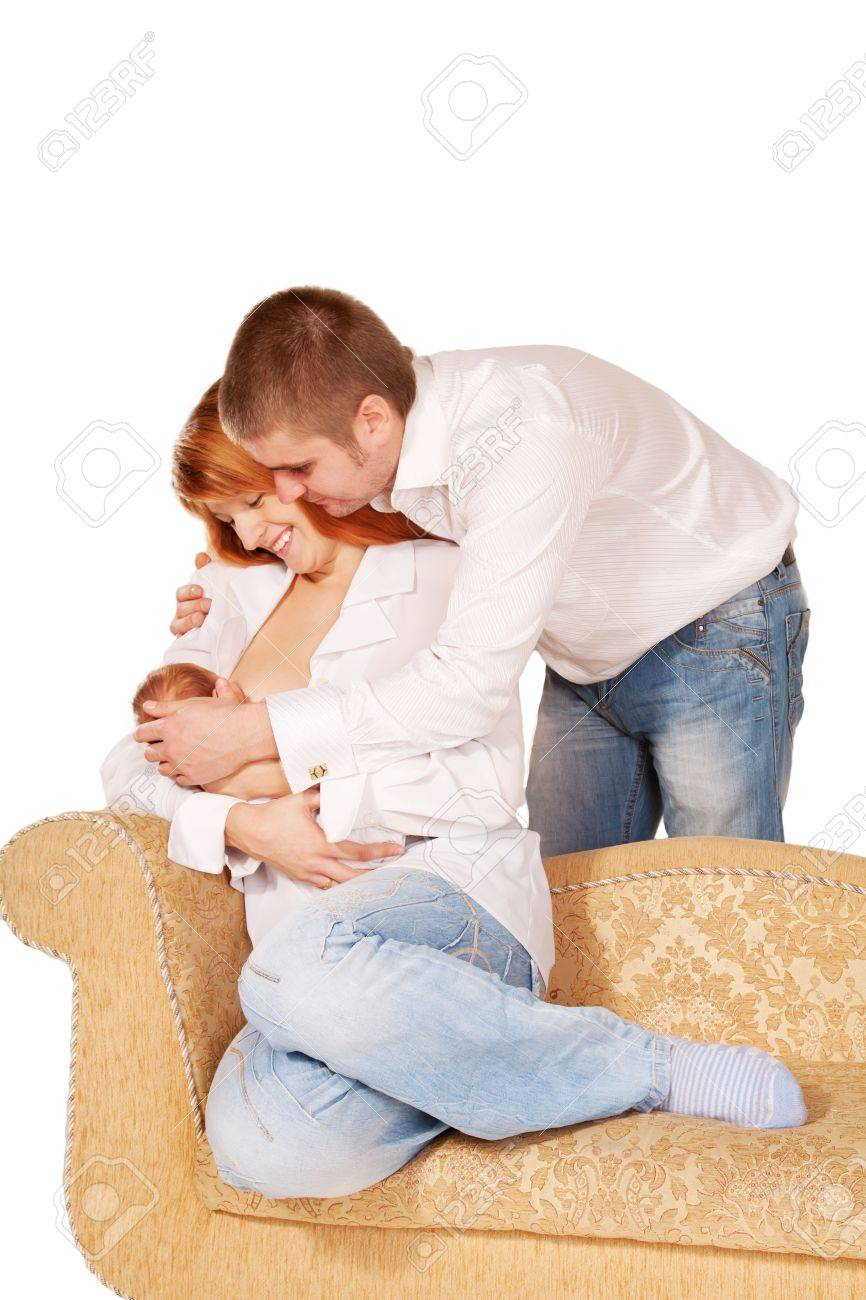 Happy young family sitting on the sofa. Mother breast-feeding newborn baby, father hugging them. Family concept. Isolated on white background Stock Photo - 16625372