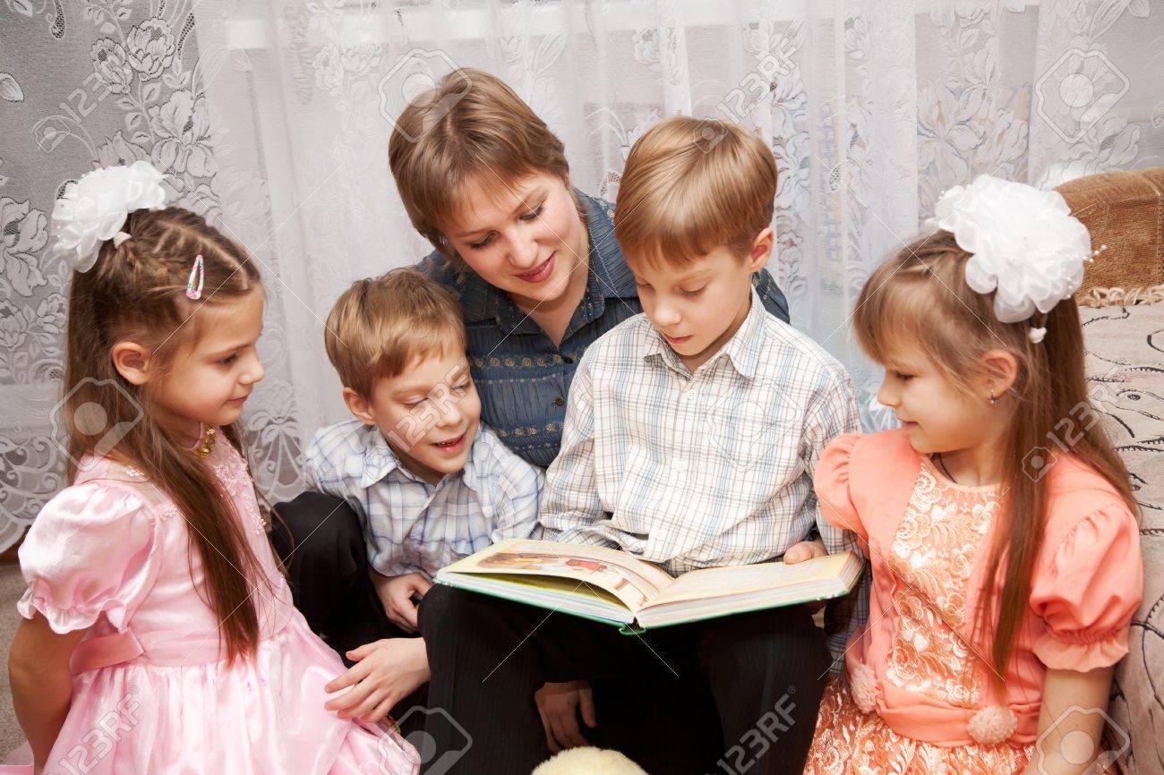 2ab1ee258e668 Banque d images - Famille concept. Heureuse mère et quatre enfants lisant  un livre. Grande famille.