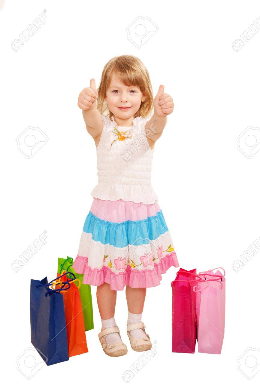 Little baby girl buyer with shopping bags showing a thumbs up..