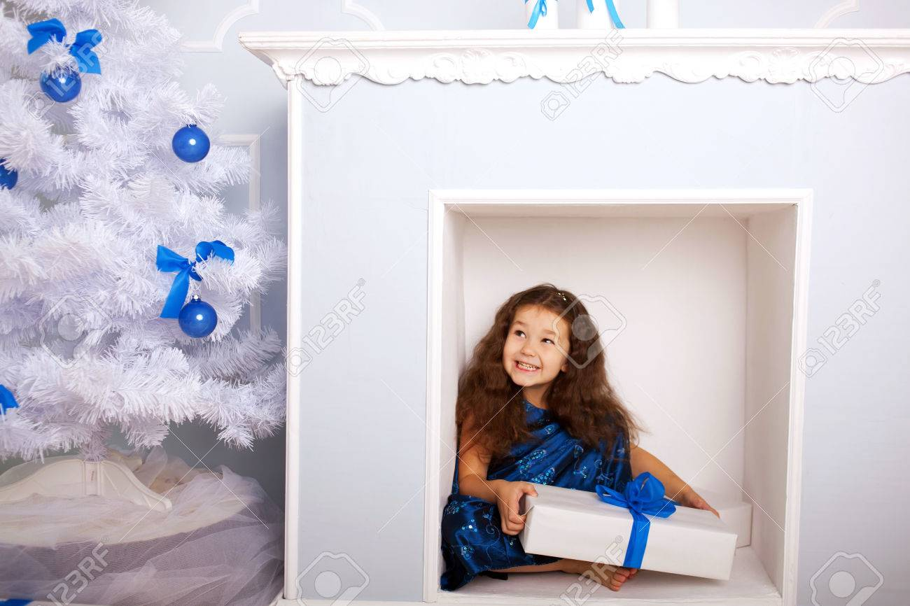 Happy smiling child sitting in the fireplace and waiting for gifts. Christmas, New Year, holiday concept, ready for your text, letters or symbols. Stock Photo - 24097015