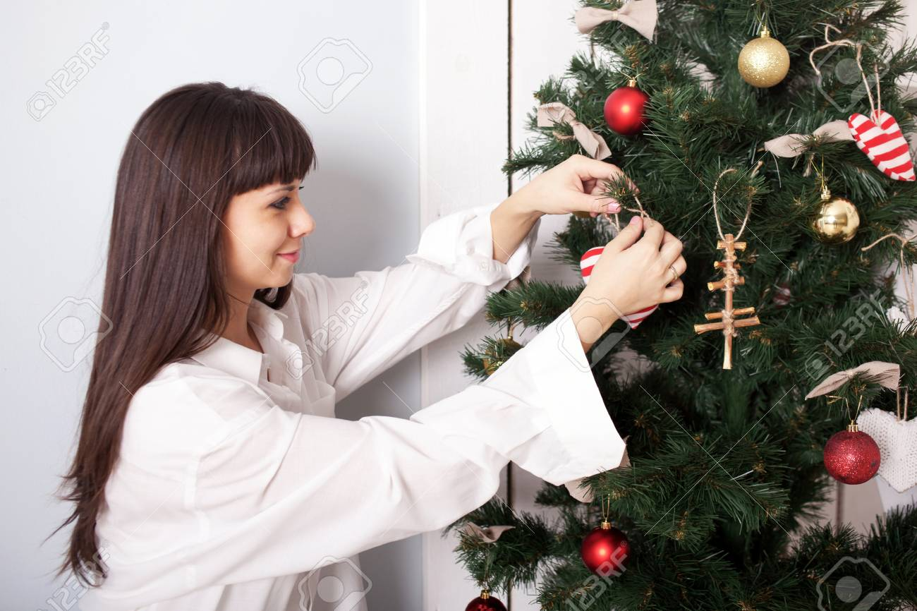 Charming woman decorating the Christmas tree with balls. Christmas Eve concept. Stock Photo - 24231300