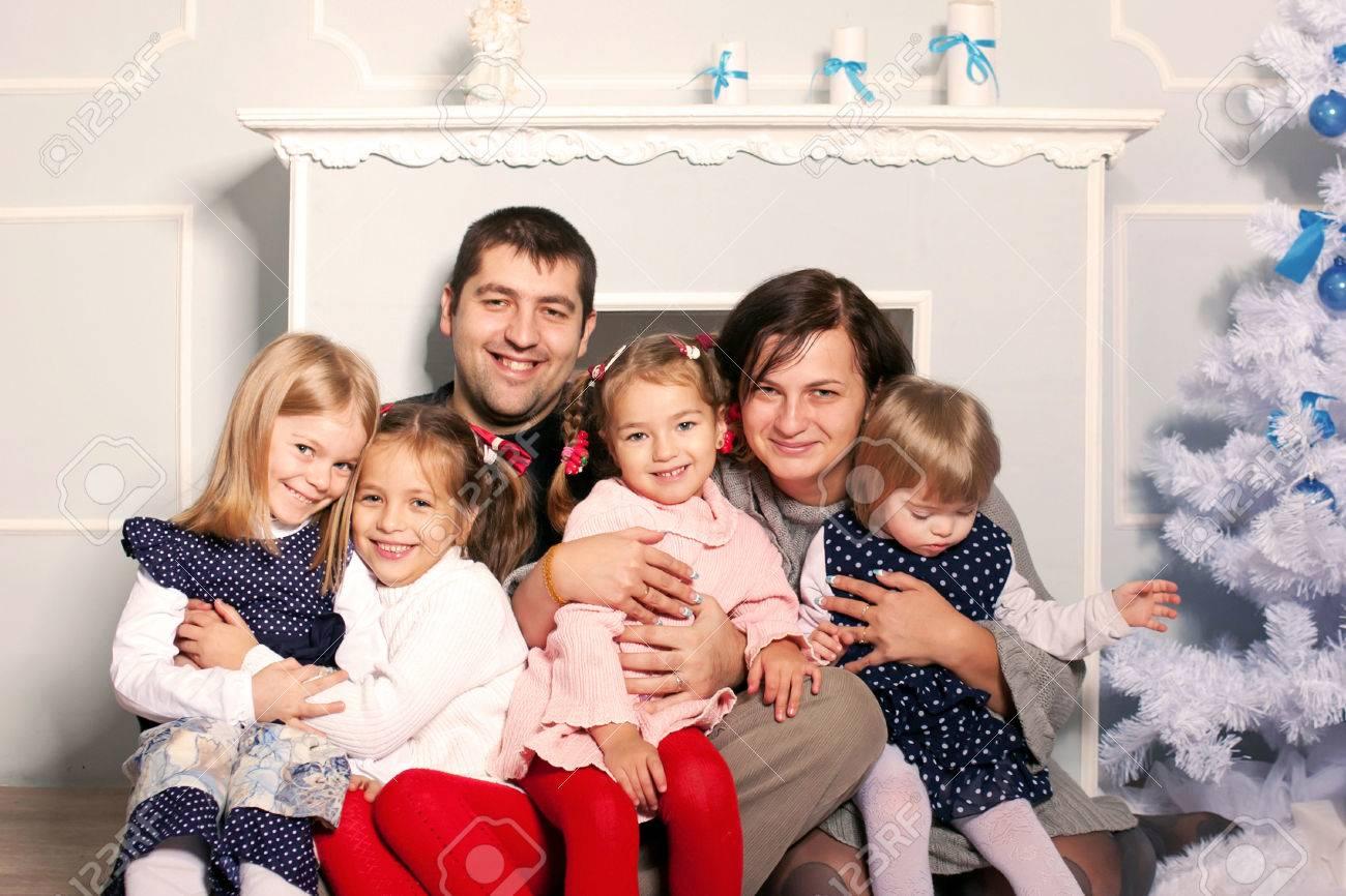 7e0df60f085a9 Banque d images - Heureux grande famille étreignant près de la cheminée et  l arbre de Noël. Père