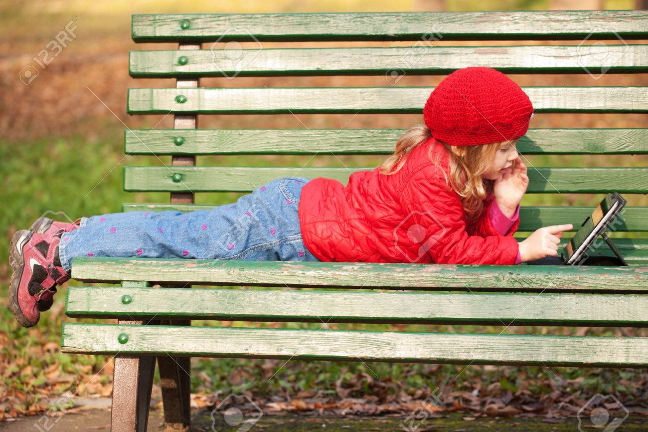 Happy little kid working with tablet pc and lying on bench in the park. Stock Photo - 24455634