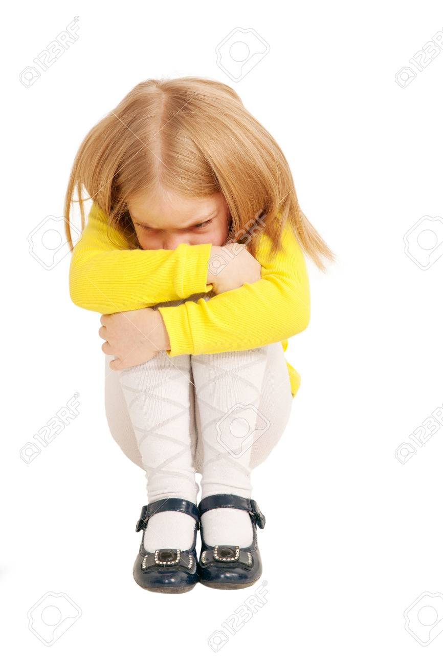 Little Sad And Upset Child Sitting Hunched Up Into A Ball Isolated