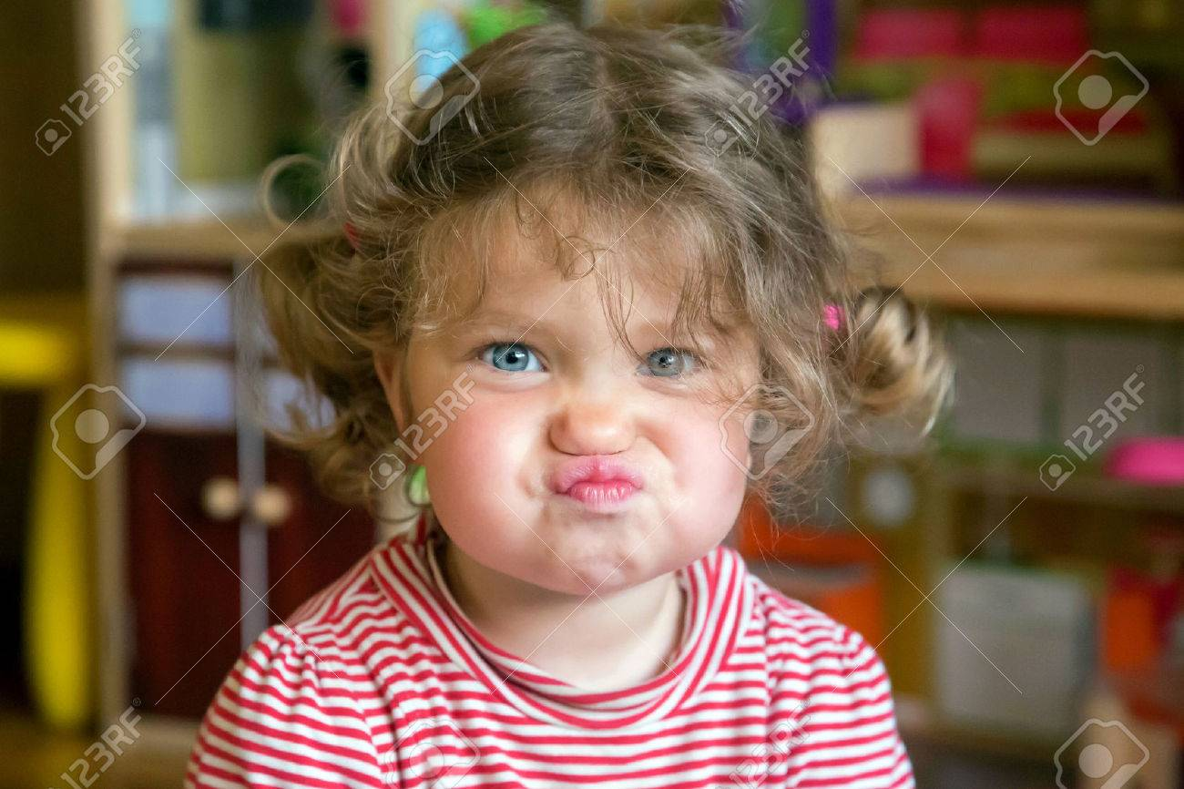 Funny portrait of adorable baby girl. Child makes grimaces face - 59700972
