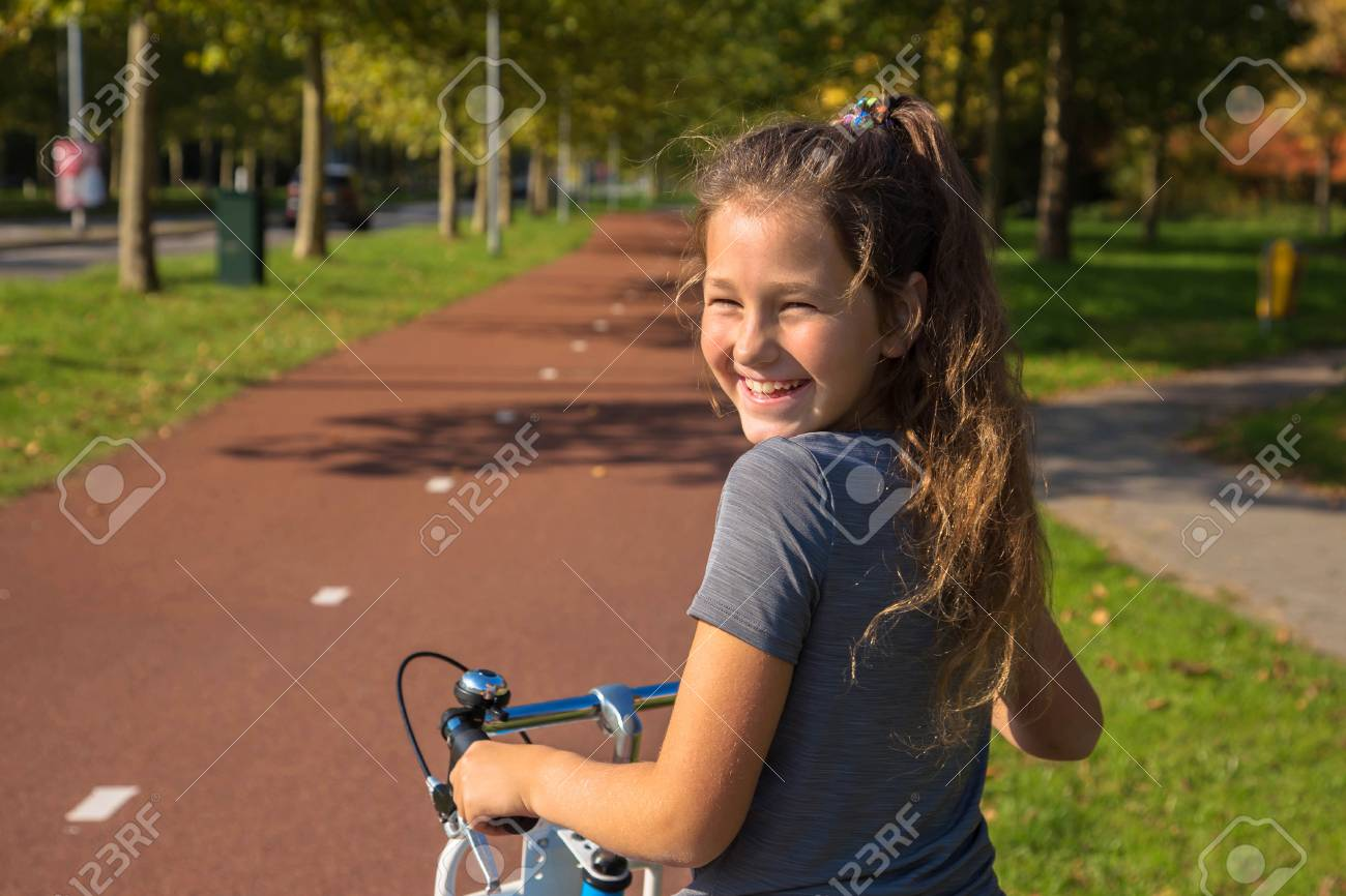 Happy child rides a bike on bike path. Cyclist child or teenager girl enjoys good weather and cycling. Environmentally friendly transport concept. Girl is smiling and laughs. Netherlands, Holland. - 117093512