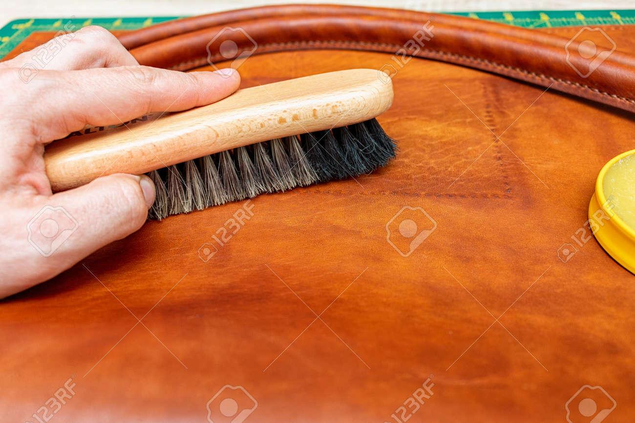Polishing handmade leather bag with brush and wax - 157265513