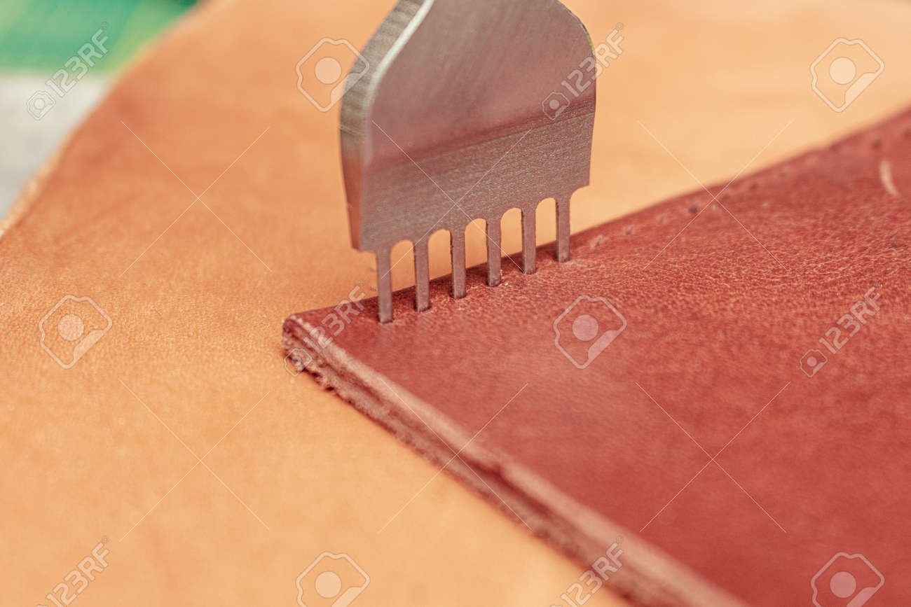 Making holes in leather with puncher tool. Sewing wallet. - 157264941