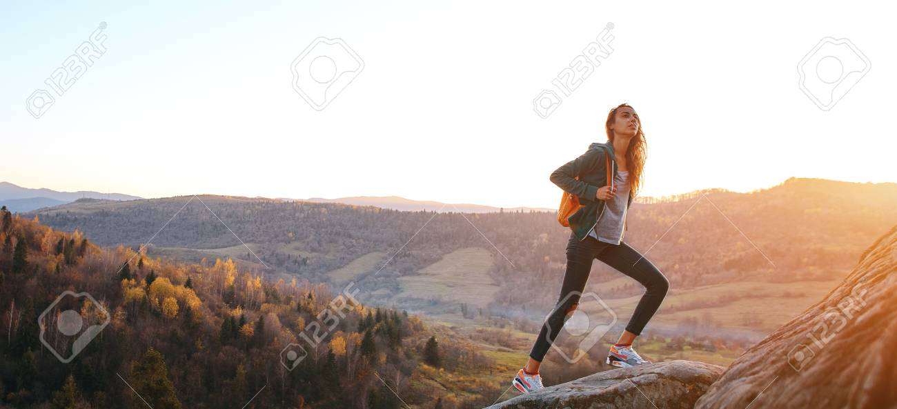 woman hiker with backpack standing on edge of cliff against background of sunrise. - 113255189