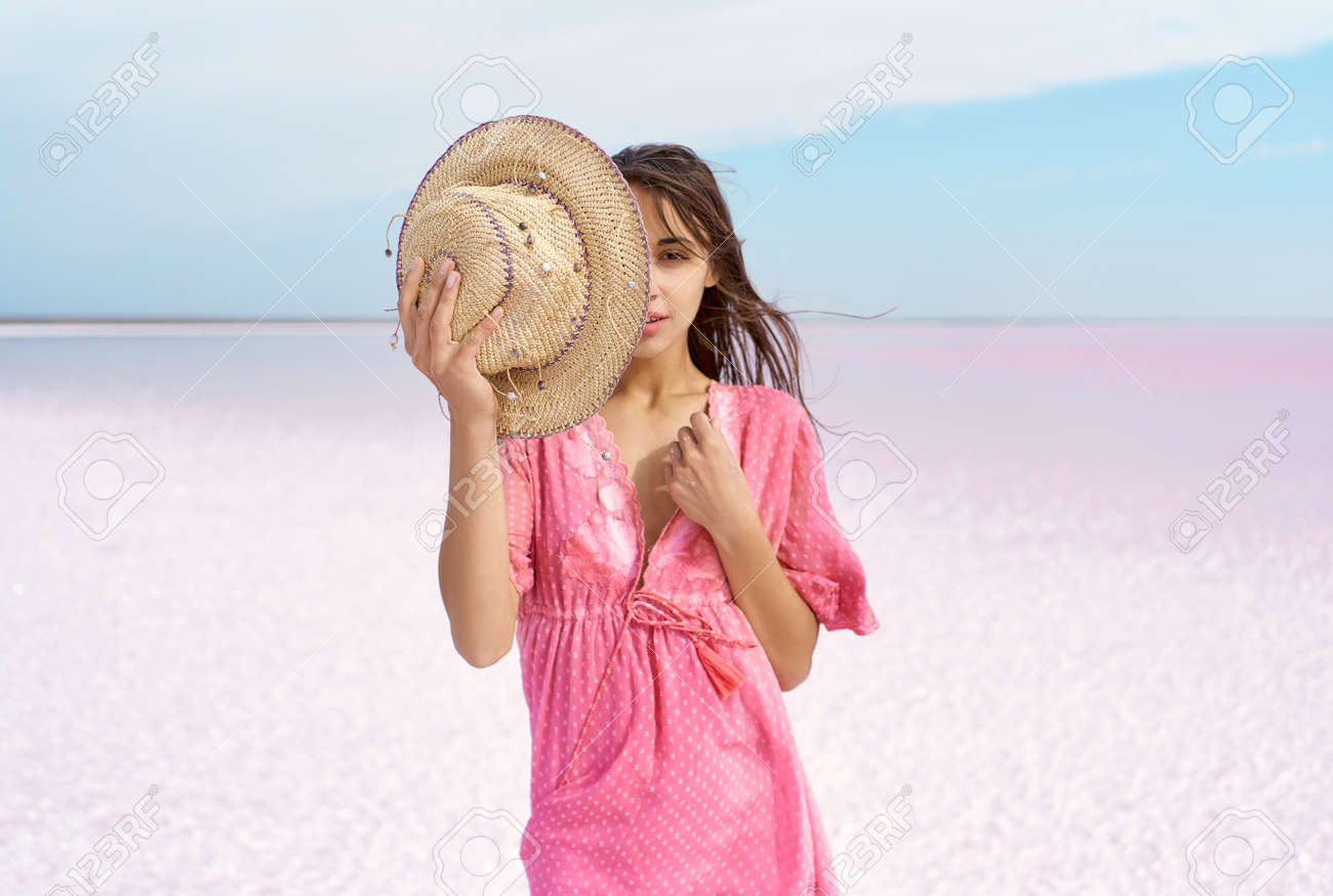 sensual portrait elegant fashion woman in pink dress on paradise landscape of salt flats on pink lake with copy space, model covering half face with hat. focus on hat - 162852364