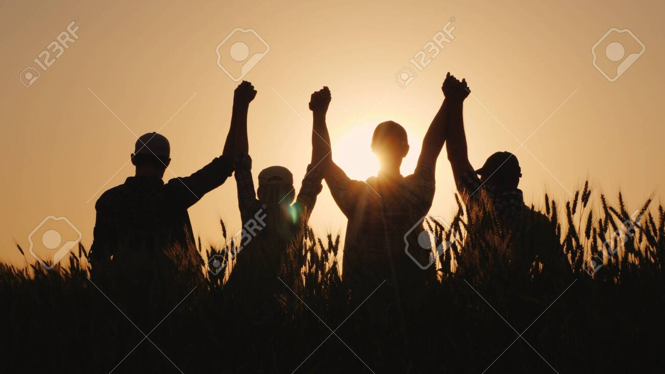 A group of successful young people hold hands, together they raise their upper hand. Successful team and team building concept. - 127245158