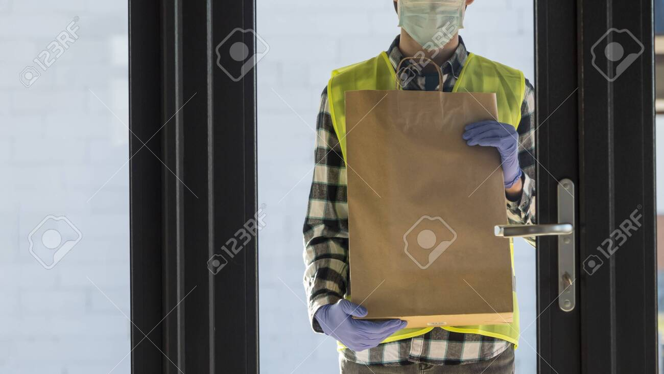 Delivery of food in quarantine, courier with a package stands at the door of the house - 143325594